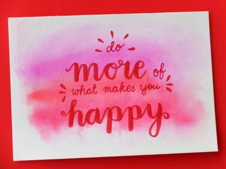 Karte mit aquarelliertem Hintergrund in Rottönen und der handgeschriebenen Aufschrift do more of what makes you happy, Foto: Janne Klöpper