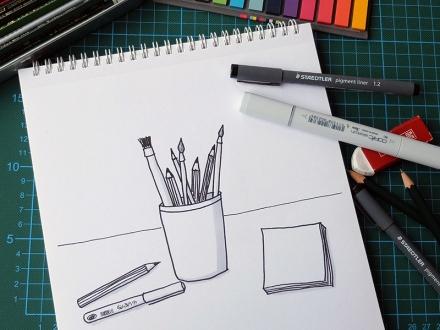 Zeichnung eines Köchers mit Stiften und Pinseln, daneben liegen verschiedene Stifte und ein Radiergummi