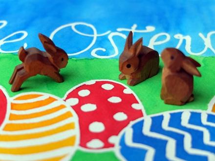 Drei kleine geschnitzte Hasen auf einem Oster-Aquarell; Zeichnung und Foto: Janne Klöpper