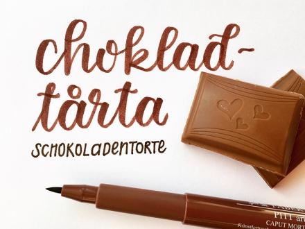 Lettering des schwedischen Wortes chokladtårta, deutsch Schokoladentorte, daneben ein Stück Schokolade und ein Stift. Lettering und Foto: Janne Klöpper