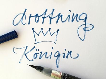Lettering des schwedischen Wortes drottning, deutsch Königin, mit einer gezeichneten Krone und einem Stift. Lettering und Foto: Janne Klöpper