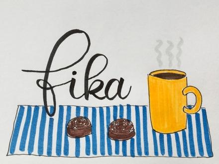 Lettering des schwedischen Wortes fika, daneben ein gezeichneter gelber Becher mit Kaffee und zwei Zimtschnecken auf einem blauweiß-gestreiften Tablett. Lettering, Zeichnung und Foto: Janne Klöpper