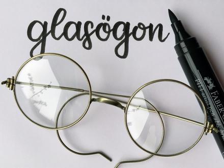 Lettering des schwedischen Wortes glasögon, daneben eine Nickelbrille und ein schwarzer Stift. Lettering und Foto: Janne Klöpper