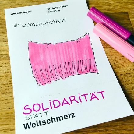 Zeichnung einer Pussyhat, einer rosa Mütze, und der Schriftzug Solidarität statt Weltschmerz. Zeichnung und Foto: Janne Klöpper