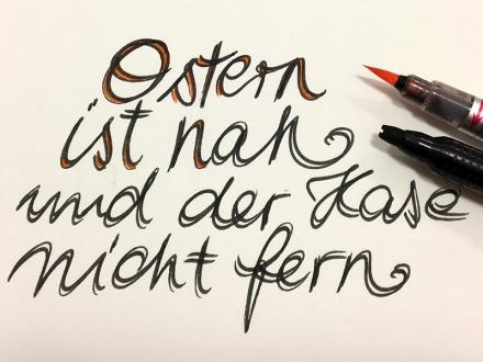 Schriftzug Ostern ist nah, schwarz mit orangen Akzenten. Lettering und Foto: Janne Klöpper