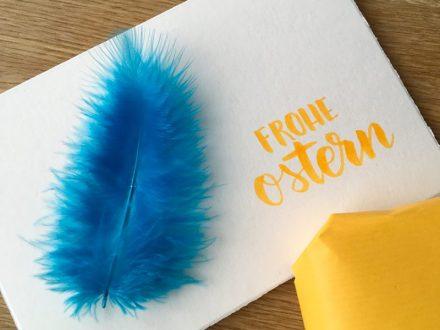 Selbstgebastelte Osterkarte mit einer Feder und dem Schriftzug Frohe Ostern als Lettering. Gestaltung und Foto: Janne Klöpper