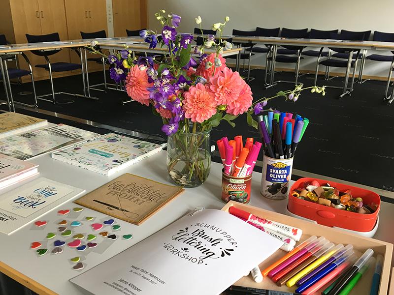 Lettering-Bücher, Brushpen, Lettering-Guide und Blumen auf einem Tisch in einem Workshop-Raum. Foto: Janne Klöpper