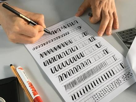 Ein Teilnehmer übt beim Lettering-Workshop die Stifthaltung. Foto: Janne Klöpper